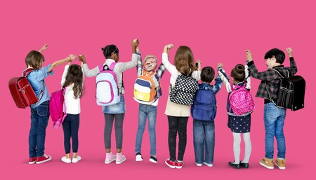 Rear view group of diverse kids standing in a row holdings hands in the air Stock Photo