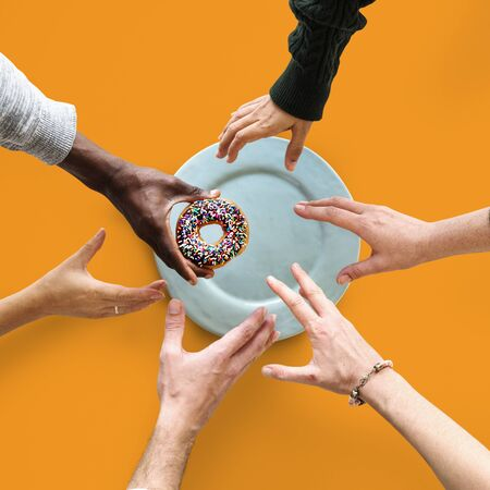 Group of Hands reaching for a donut Banco de Imagens