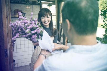 お客様がお花屋さんで花束を拾いに来る 写真素材