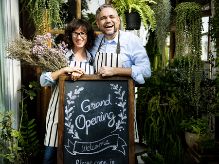 Adult Man and Woman Standing with Grand Opening Sign Imagens