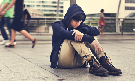 Asian Guy Sit on the Street Depression Stockfoto