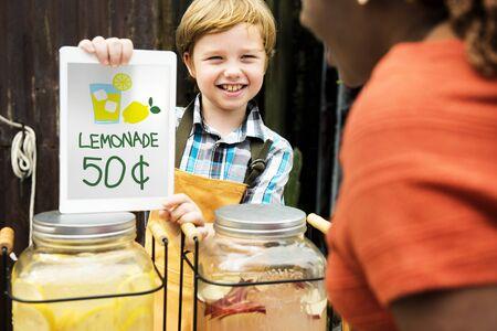 フード ストール マーケットでレモネードの価格を示す小さな男の子