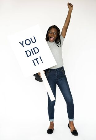 African girl holding you did it banner studio portrait