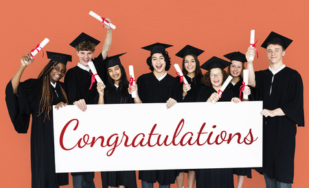 spolužák: Diverse Students wearing Cap and Gown Showing Congratulations Sign Studio Portrait Reklamní fotografie