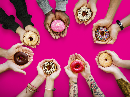 Hands holding donuts Stock Photo