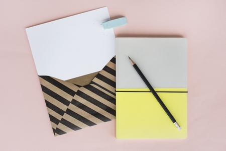 Stripe Envelope com papel e caderno em fundo rosa Foto de archivo - 80937544