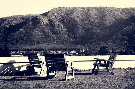 Empty Chairs on Grass Field Among Mountains Nature