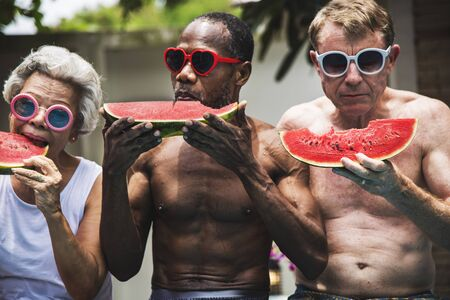 Group of senior friends eating watermelon on the poolside
