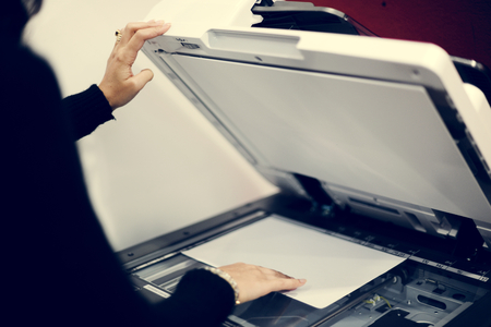 Woman using machine to copy document Stock Photo