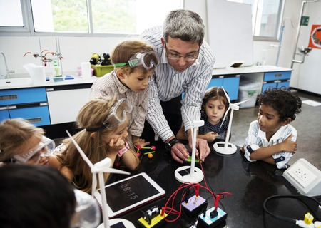 Diverse kindergarten students learning energy producer from solar windmill in science class Stockfoto