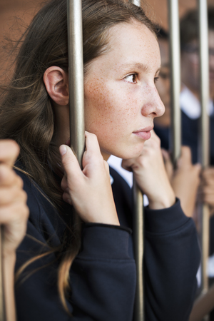 Young sad and boredom schoolgirl holding at the gate Stock Photo