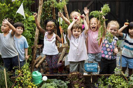 Kinder sind im Garten, der die Pflanzen bewässert