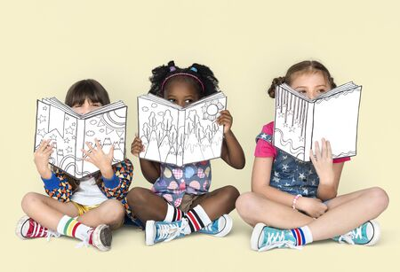 Little Children Reading Sitting Down Stock Photo