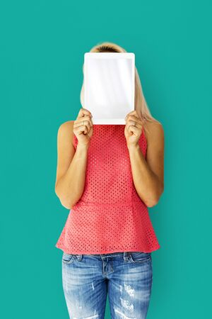 techie: Woman holding tablet cover her face Stock Photo