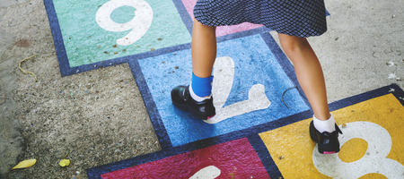 Young girl playing hopscotch