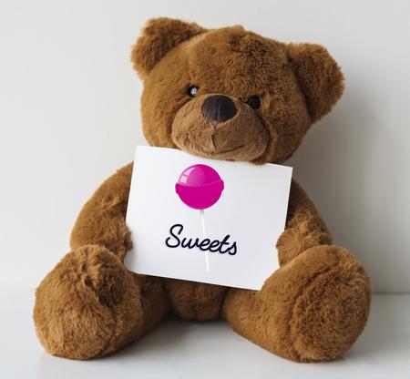 Teddy bear with illustration of sweet candy lollipop Фото со стока