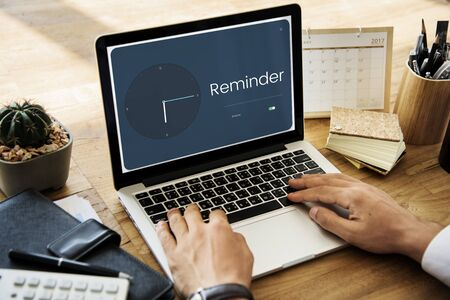 People using laptop with clock and time icon Stock Photo