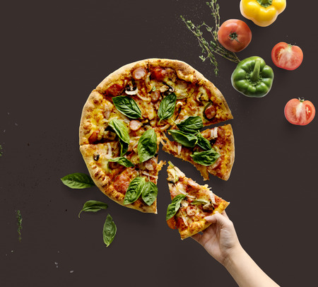 Hand nemen een stuk Italiaanse keuken pizza Stockfoto