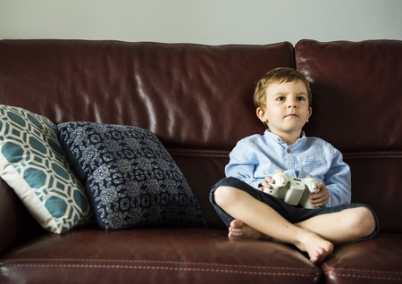 Little boy sitting and playing video games on the couch