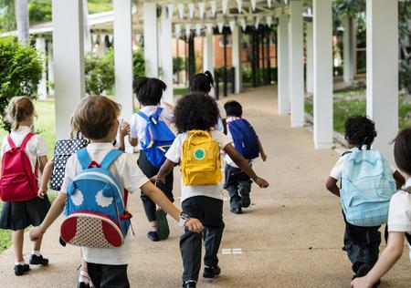 一緒に歩いて多様な幼稚園生のグループ