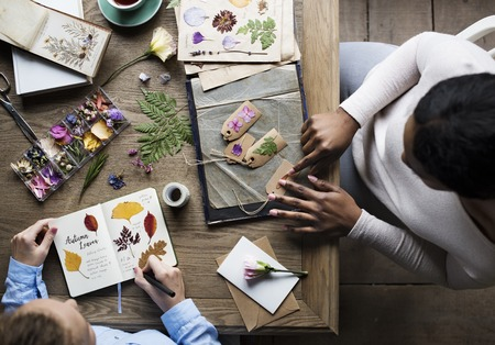 dried flower arrangement: Hands Making Attach Dried Flowers Collection in Notebook Handmade Work Hobby