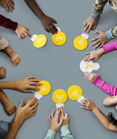 Aerial group of kids hands holding light bulb icon