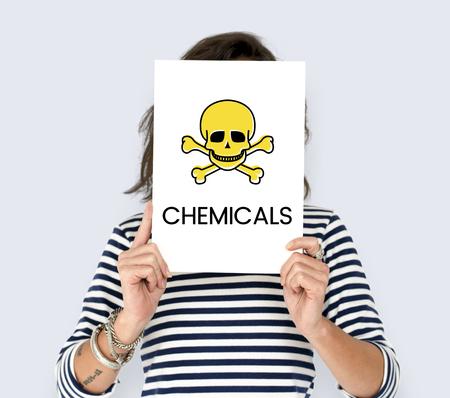 持っている人は placard スカル アイコンおよび危険な化学薬品と 写真素材