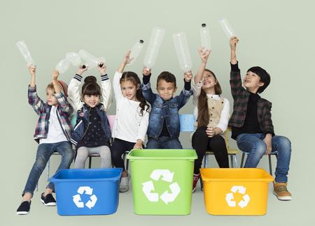 휴지통에있는 어린이 및 플라스틱 병 스톡 콘텐츠