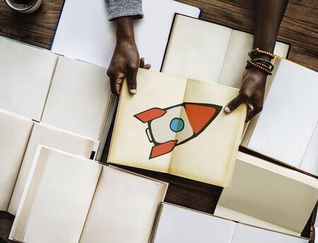 手のロケットで本を開くアイコンを起動します。 写真素材