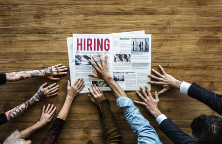 Diverse People Hands Reach Out for Hiring Newspaper Announcement