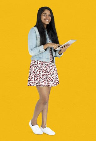 Young indian woman standing and using digital tablet