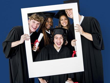 spolužák: Rozmanité studenty na sobě Cap a Gown Holding fotorámeček Studio Portrét Reklamní fotografie