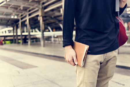 Man holding notebook and walking in the city