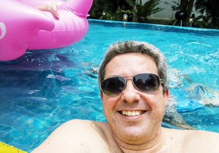 Man with sunglasses floating in a pool