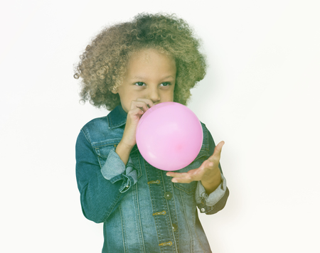 Young boy standing and blowing ab balloon Stock Photo