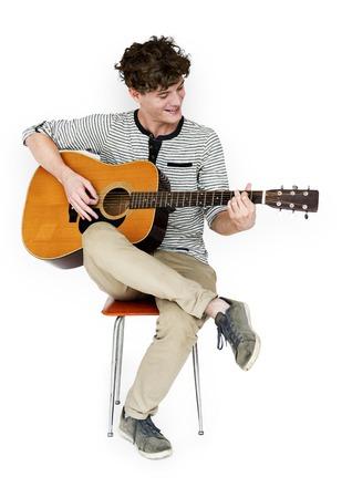 男性ギタリスト プレーヤーに座って、ギターを弾く