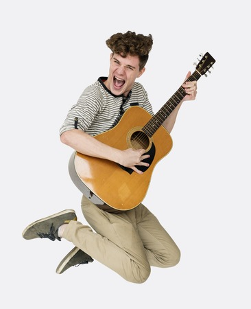 ギターの笑顔とジャンプ スタジオ ポートレートと若い成人男性 写真素材