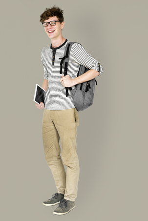 techie: Caucasian young man standing with backpack and tablet