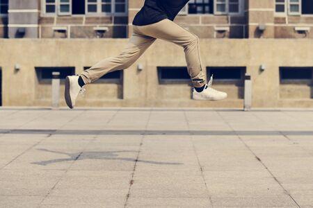 대학 캠퍼스 건물의 frount에서 점프 젊은 남자 스톡 콘텐츠