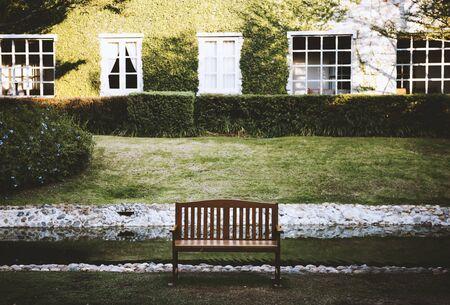 ベンチは緑の芝生の庭の前でリラックスします。