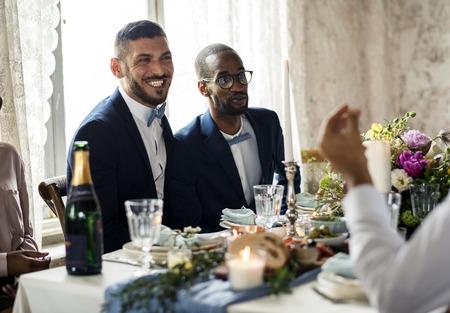 Newlywed gay couple at wedding reception Stock Photo