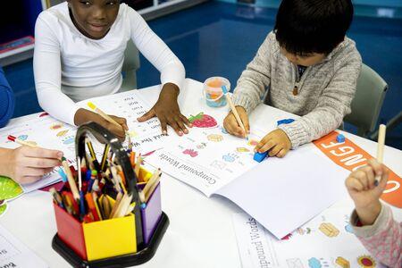 Groep diverse kinderen kleuren werkboek in de klas Stockfoto