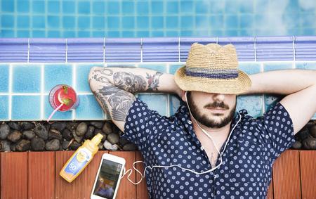 수영장 옆 백인 남자 수면 sunbath 및 듣기 음악