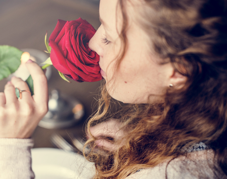 Woman holding flower and smelling it