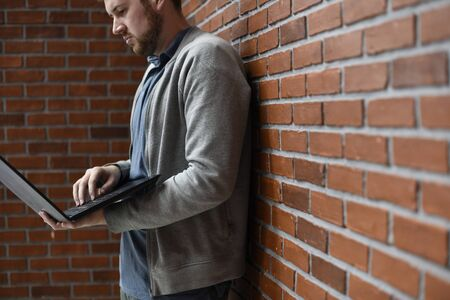 Man lean on brick wall and using laptop