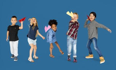 Diverse groep kinderen die papierplannen lanceren