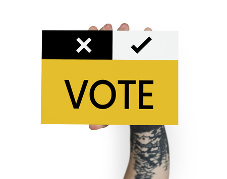 Hnads with tattoo hold vote card Banco de Imagens