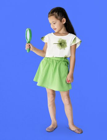 A girl is holding green magnifier Stock Photo