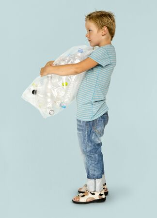 niños reciclando: Ecology little boy holding bag of plastic bottle for recycle
