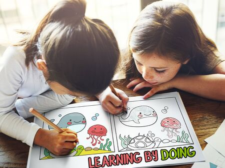 best book: Children working on book network graphic overlay Stock Photo
